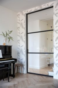 interieur met zwarte stalen deur, visgraatvloer en behang met palmbladeren