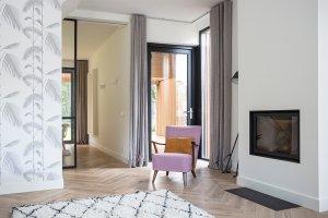 interieur met open haard, visgraatvloer, behang met palmbladeren en een doorkijkje naar de keuken en de veranda