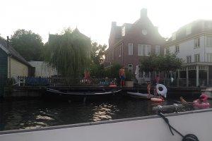 Huizen langs de vecht en zwemmers in het water