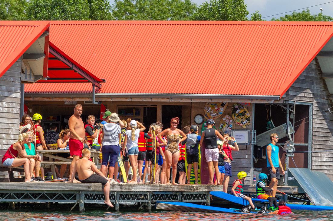 gasten van campin Betuwestrand in de zon op het startplatform van de waterskibaan