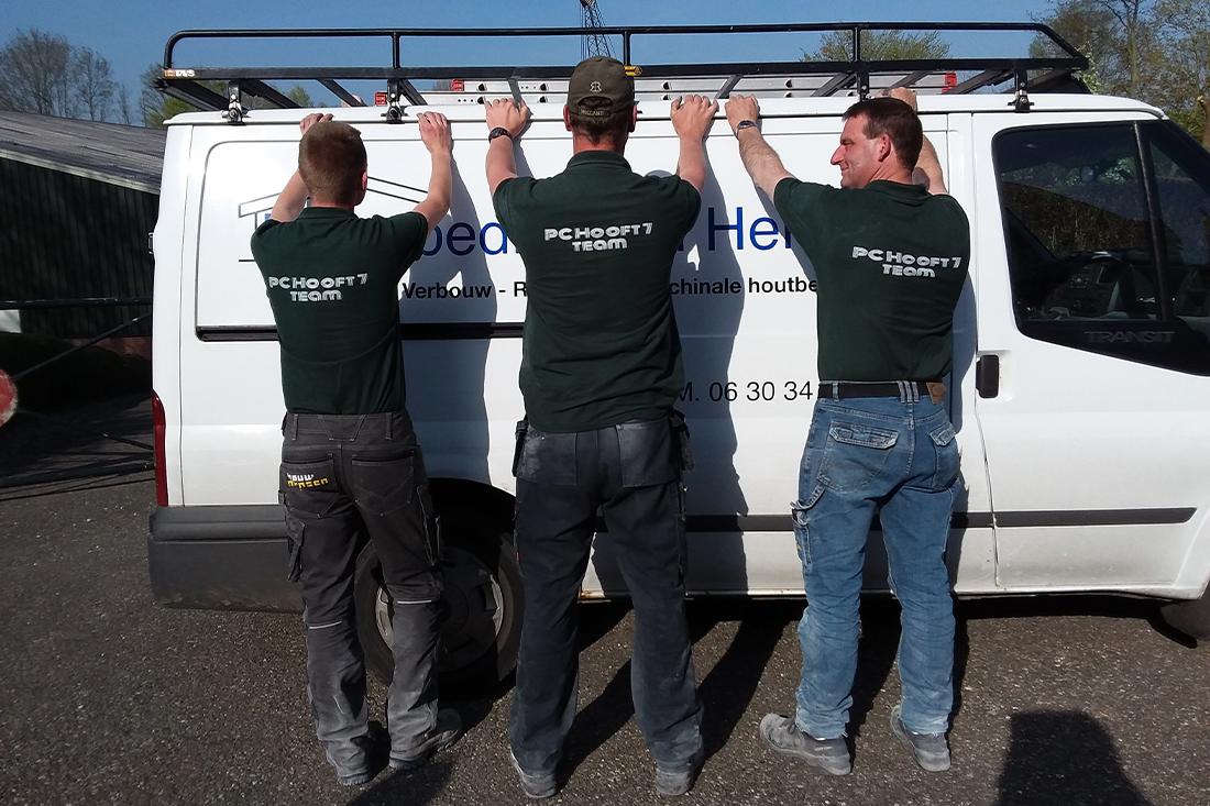 bouwteam poseert met t-shirts voor de bus van de aannemer