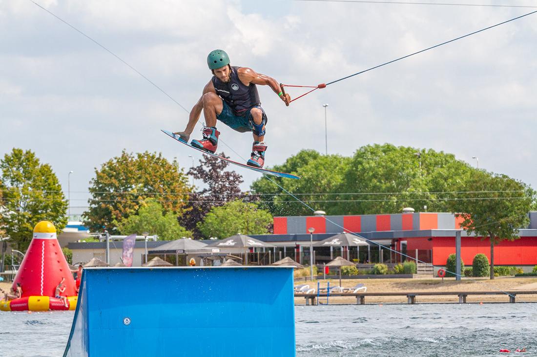man hangt in de lucht boven een waterski schans