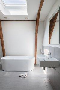 badkamer op zolder met modern vrijstaand bad, strak wit stucwerk, veel licht via een daklicht en de oude houten spanten in het zicht.